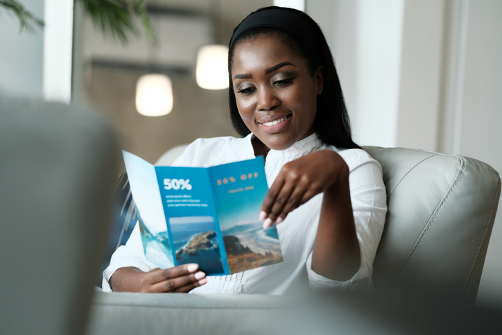 African American Woman Sitting On Sofa, Reading A Travel Flyer Advertising Promotional Discounts For Vacations. (African American Woman Sitting On Sofa, Reading A Travel Flyer Advertising Promotional Discounts For Vacations., ASCII, 112 components, 11
