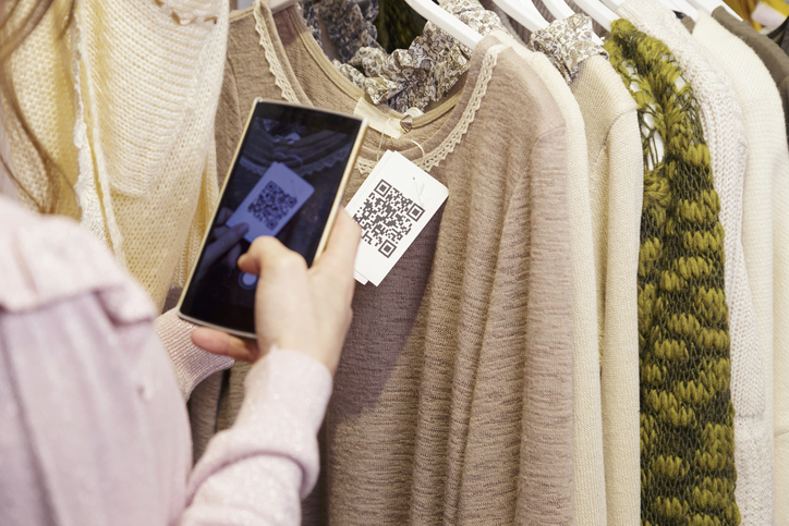 Woman scanning a QR code, with her smart phone, from a label in a clothing store. No face.